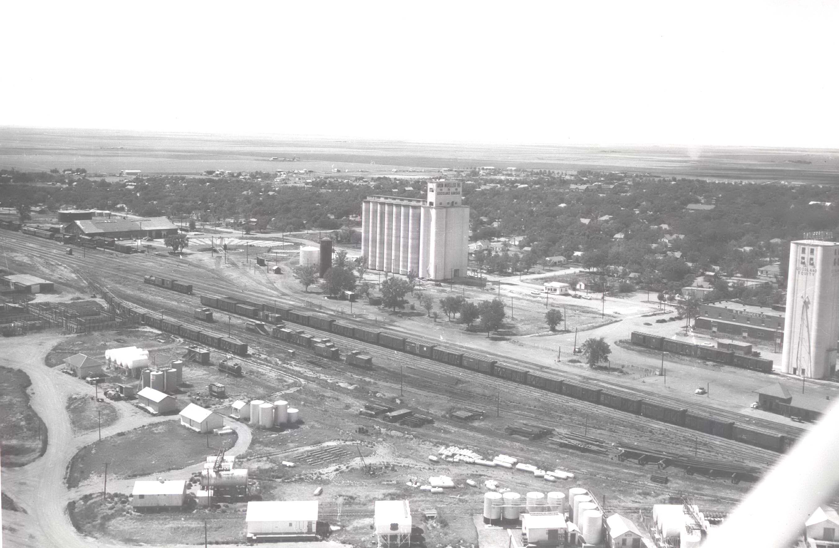 High Plains Museum | PM221BUILD Aerial view of Goodland looking Northwest from the Rock Island Railroad yards.  Mueller Grain & Co-op elevators in photograph.  Circa 1950.